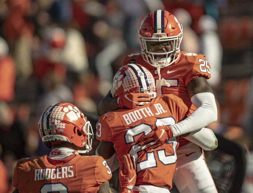 Clemson safety Jalyn Phillips (25) celebrates a defensive stop with cornerback Andrew Booth Jr. (23) during the second half of an NCAA college football game Saturday, Oct. 31, 2020, in Clemson, S.C. (Josh Morgan/Pool Photo via AP)