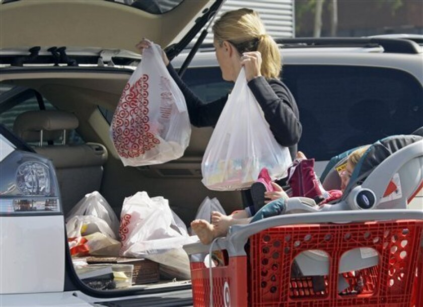 A woman with a child loads purchases from a Target store into her car in Culver City, Calif., in September. State rules are being crafted to reduce the amount of harmful ingredients in common products, from electronics to cosmetics. (AP Photo/Reed Saxon)