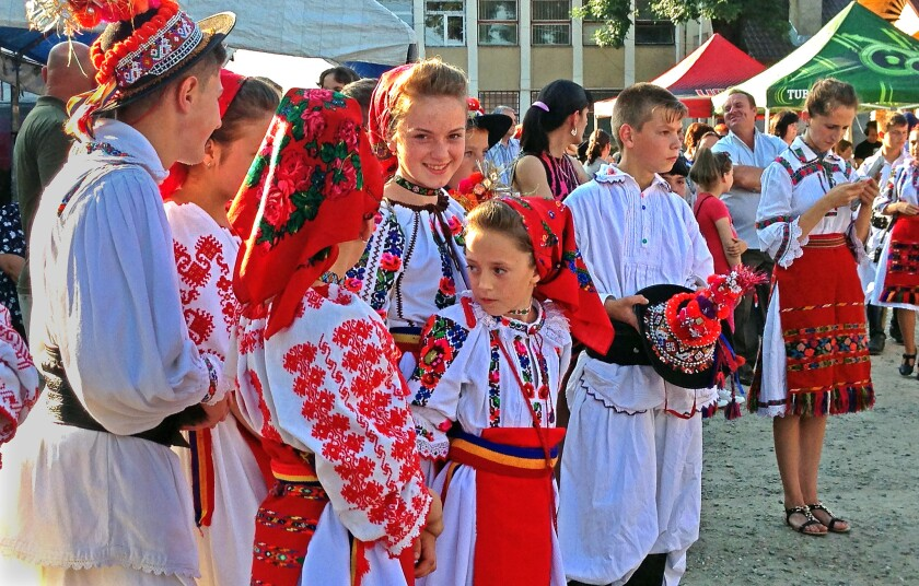 Romanian youths wearing traditional peasant dress wait to perform at a county fair in Romania's Maramures region. Traditional clothing is still worn for church or special occasions.