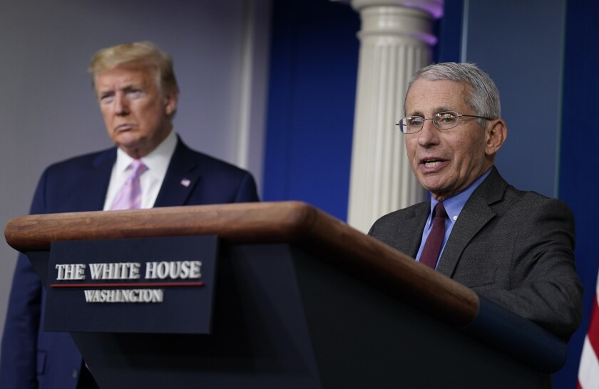President Trump listens as Dr. Anthony Fauci, the director of the National Institute of Allergy and Infectious Diseases, speaks during a coronavirus briefing at the White House earlier this month. In recent days, their relationship has been fraught.