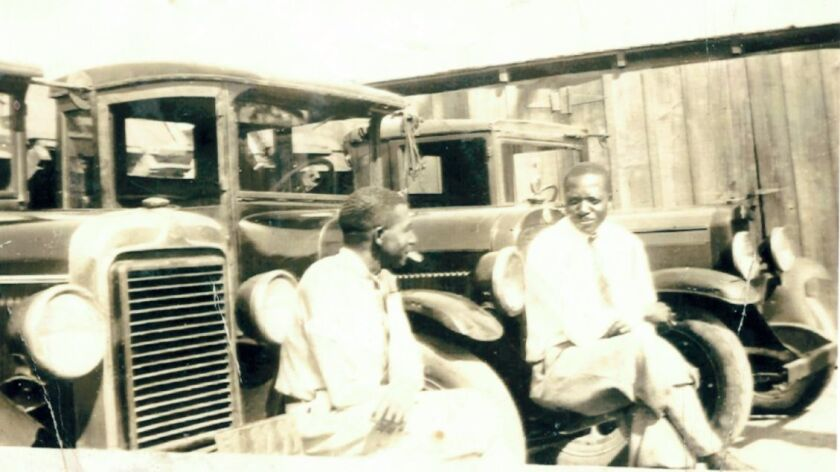 Ed Coleman and his neighbor John Townsend in 1926 with the trucks Coleman used to move cottages around La Jolla.