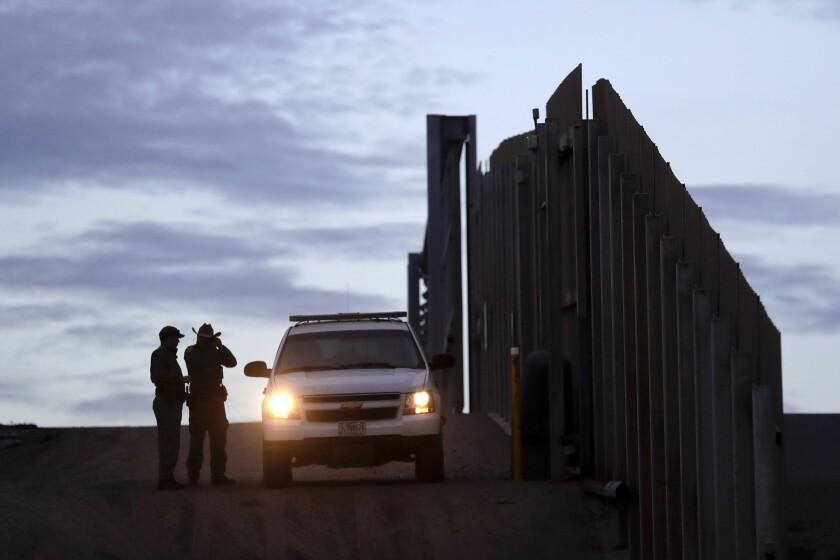 En esta imagen del 21 de noviembre de 2018, agentes de la Patrulla Fronteriza junto a uno de sus vehículos