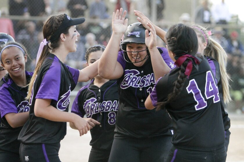 Carlsbad's Adriana Huetter (center) is swarmed by teammates after her bunt in the sixth resulted in two runs and a 3-2 lead for the Lancers, who will play for the Division I title.