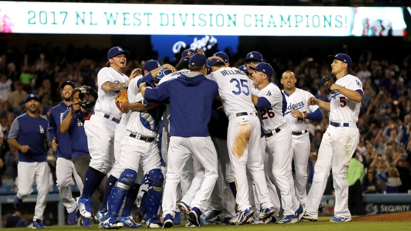 The Dodgers celebrate after beating the Giants at Dodger Stadium on Friday night to clinch the NL We
