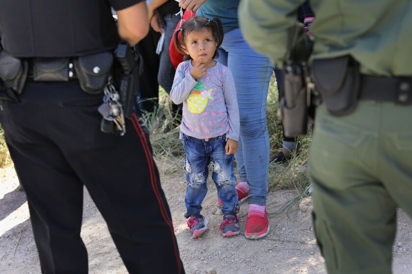 A Mission Police Department officer, left, and a U.S. Border Patrol agent watch over Central American asylum seekers before taking them into custody on June 12 near McAllen, Texas.
