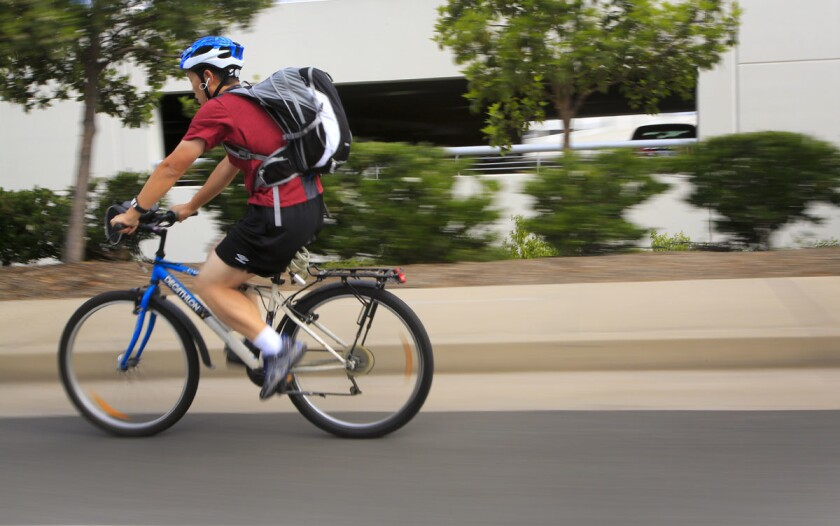A bicyclist rides along Mira Mesa Boulevard during Bike to Work Day 2016. (Howard Lipin/Union-Tribune)