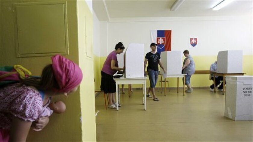 A young girl holding her doll peeps into a room as residents cast their votes during general elections in Bratislava, Slovakia, Saturday, June 12, 2010. Slovakia's three party governing coalition is fighting for survival in a parliamentary election on Saturday, challenged in a tight race by the cen