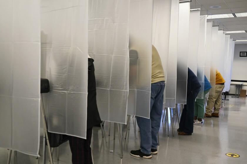 Votantes llenan sus boletas en votaciones tempranas en la Junta Electoral del Condado Cuyahoga