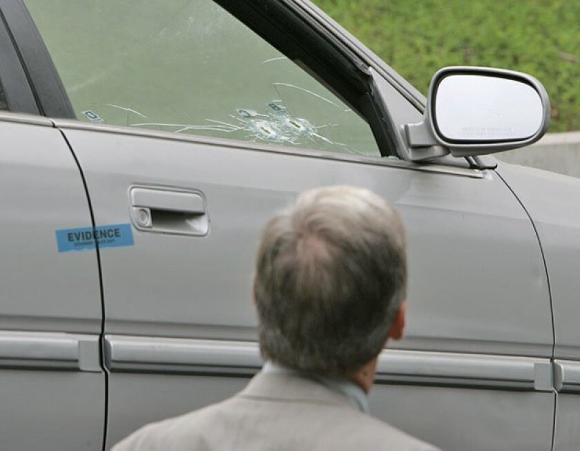 Prosecutor Jeff Dusek inspected the Honda Accord driven by Rachel Silva in the March 15, 2008, incident in which an off-duty police officer fired shots at Silva's car. (Charlie Neuman / Union-Tribune)