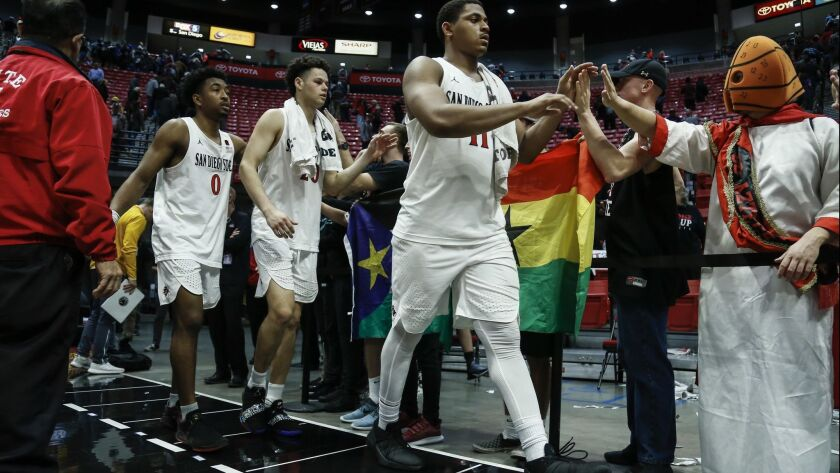 SDSU's Matt Mitchell (right), Jordan Schakel (center), and Devin Watson (left) high-five students after beating Wyoming 84-54 on Tuesday night at Viejas Arena.