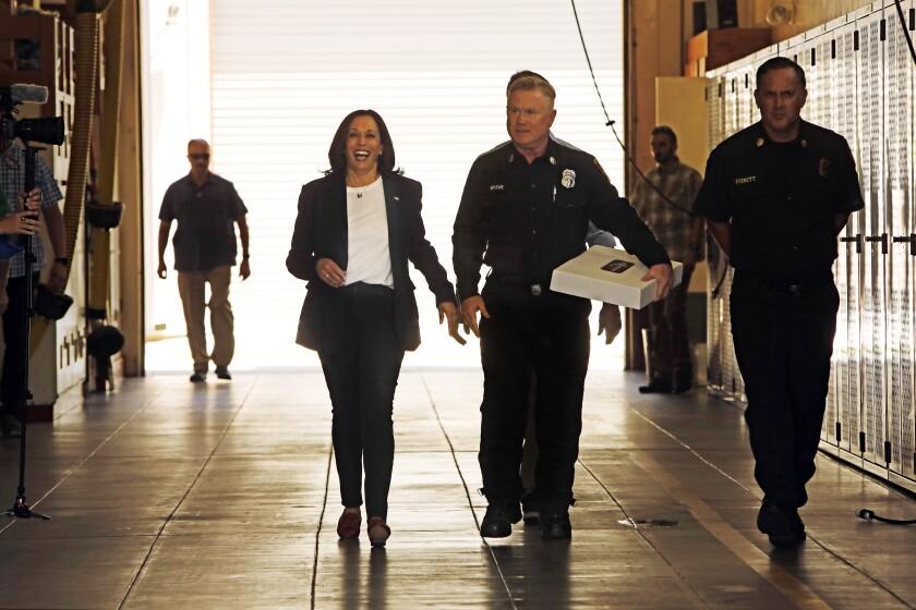 Vice President Kamala Harris walks in uniform with two men