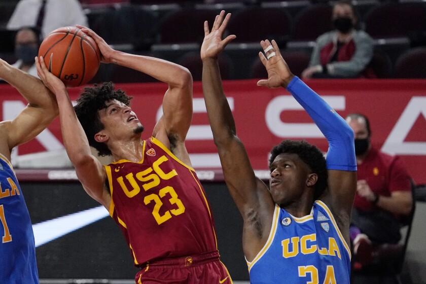 USC forward Max Agbonkpolo shoots over UCLA guard David Singleton.