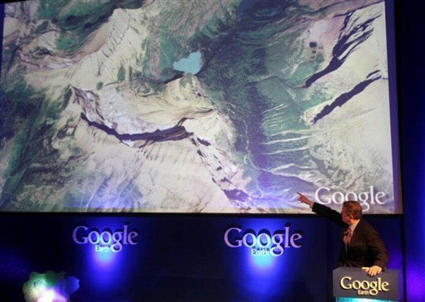 Former Vice President Al Gore points at a screen showing the new Google Earth 5.0 at the California Academy of Sciences in San Francisco, Monday, Feb. 2, 2009. Google Inc. is launching a new version of Google Earth that will let users explore the oceans, view images of Mars and watch the Earth's surface change over time. (AP Photo/Jeff Chiu)