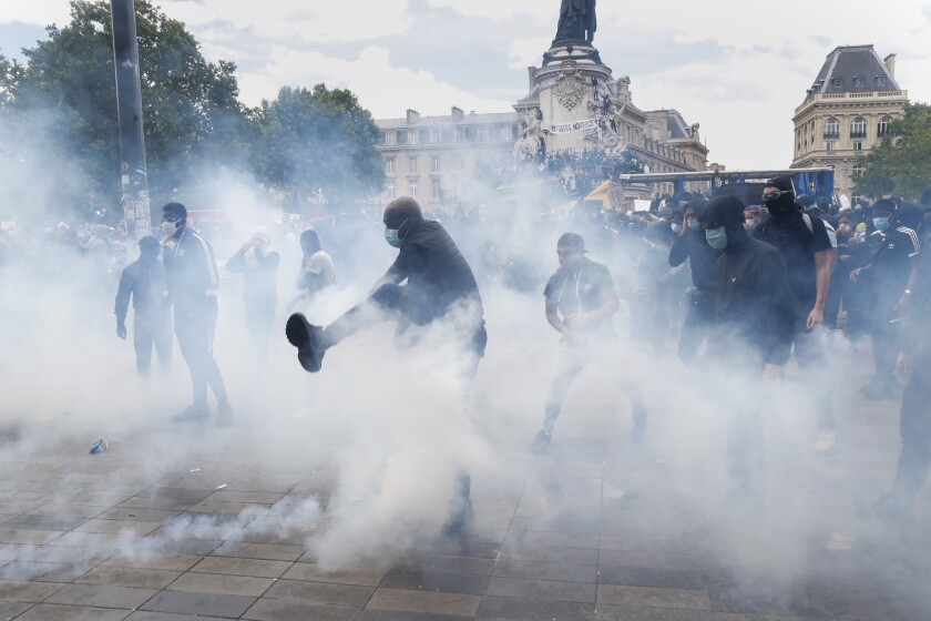 Tear gas drifts around protesters on the streets of Paris