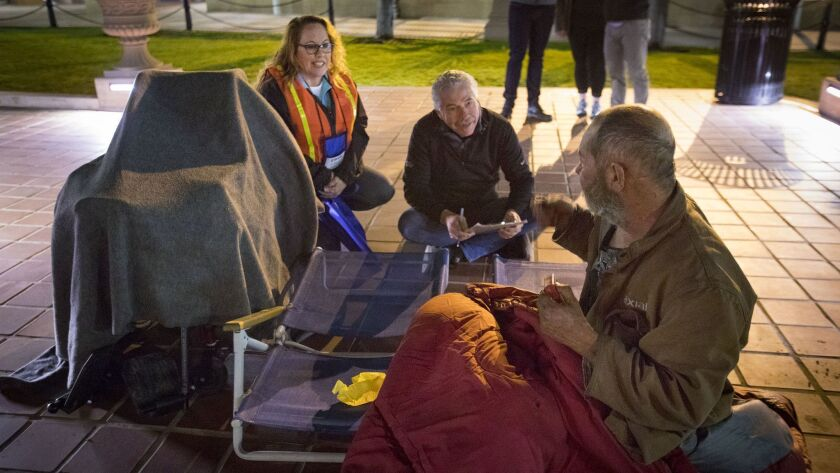 Jill Kernes, left, and Bill Geppert, center, conduct a survey with John Ross, right, who had been sleeping near the fountain in Horton Plaza, during the annual point-in-time homeless count before dawn on Friday.