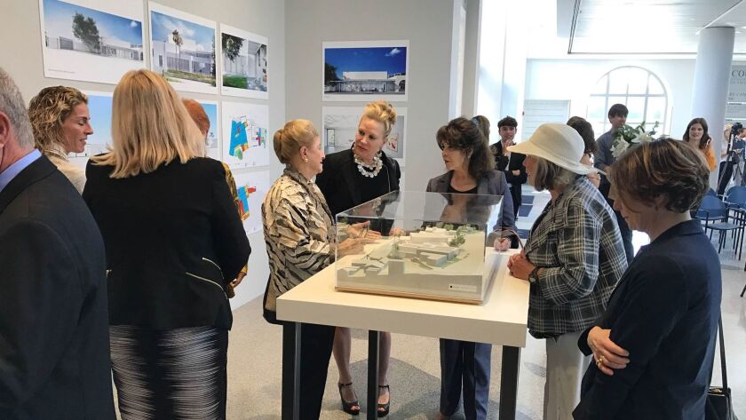 Museum patrons examine a model of the museum expansion plans. An unspecified challenge grant from Joan and Irwin Jacobs attracted major donations from 15 other families and foundations, the museum said.