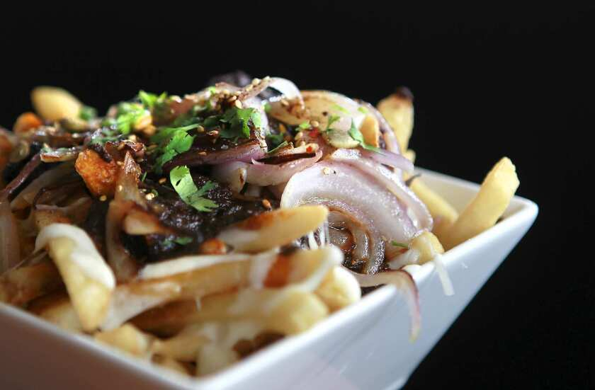 A dish of mole fries with mole poblano gravy, melted cheese, grilled onions and fries at Ricardo Diaz's new restaurant Bizarra Capital.