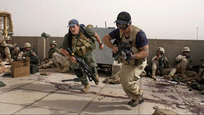 In this April 4, 2004 file photo, plainclothes contractors working for Blackwater USA take part in a firefight as Iraqi demonstrators loyal to Muqtada Al Sadr attempt to advance on a facility being defended by U.S. and Spanish soldiers in Najaf, Iraq.