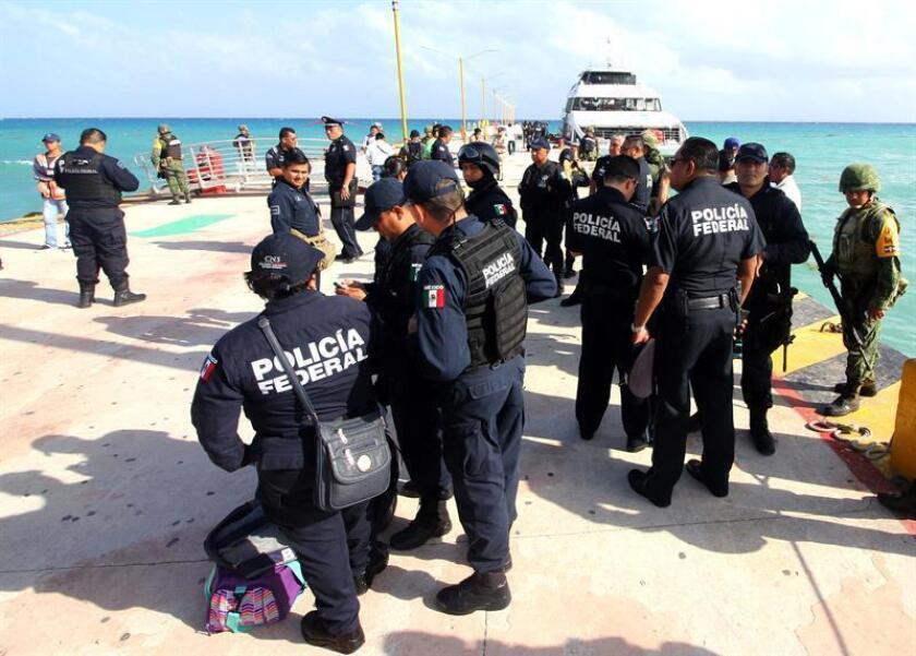 MEX64. PLAYA DEL CARMEN (MÉXICO), 21/02/2018.- Policías Federales vigilan una embarcación hoy, miércoles 21 de febrero de 2018, en Playa del Carmen Quintana Roo (México). Unas 18 personas, entre ellas tres turistas canadienses, resultaron heridas por la explosión de un barco en Playa del Carmen (sureste de México), informaron hoy fuentes oficiales. EFE/Alonso Cupul