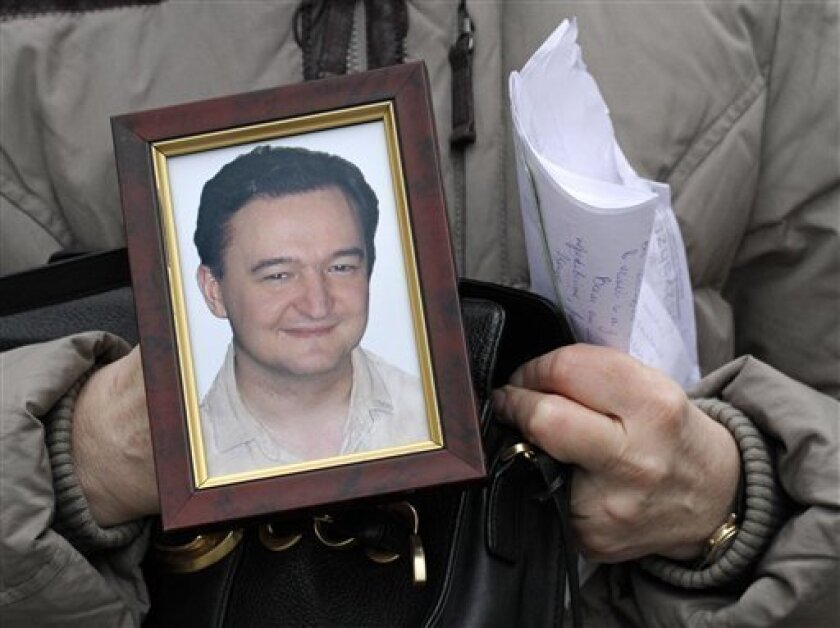 FILE - In this Nov. 30, 2009 file photo, Nataliya Magnitskaya holds a portrait of her son, Russian lawyer Sergei Magnitsky, a lawyer who died in jail, as she speaks  with The Associated Press in Moscow, Russia. The Treasury Department on Friday announced the names of 18 Russians subject to financia