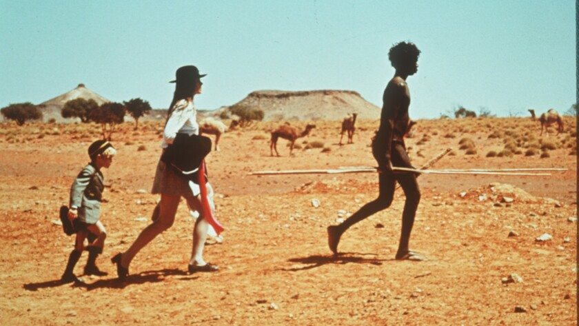 """David Gumpilil, right, leads Lucien John and Jenny Agutter in the 1971 Nicolas Roeg film """"Walkabout."""""""