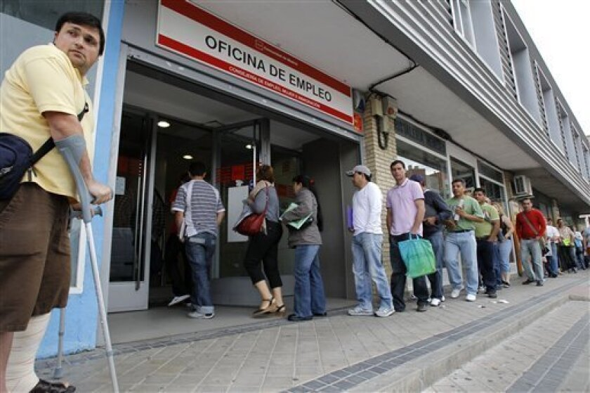 People stand in line outside a government job center on Wednesday, June 2, 2010 in Madrid. The number of people seeking unemployment benefits in Spain fell by more than 76,000 in May, the second straight monthly decline, but over the past 12 months the number of people seeking benefits has increased by 12.3 percent, or 446,063, to a current total of 4,066,202. (AP Photo/Victor R. Caivano)