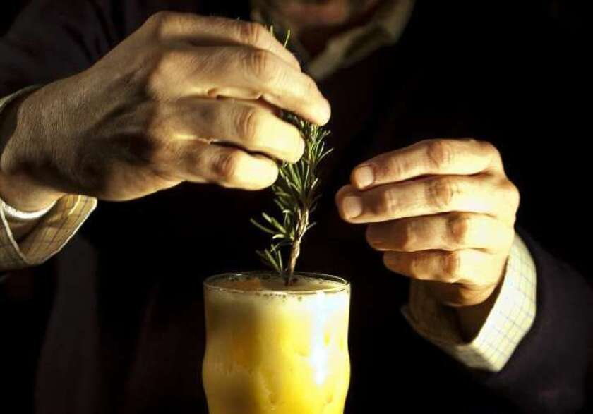 Bartender Matthew Biancaniello garnishes a hops-infused-gin cocktail with a sprig of rosemary.