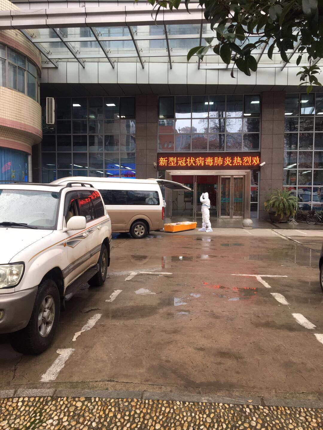 Mr. Yang sat in his car in front of a hospital, watching funeral workers load corpses into vehicles to be cremated. Every body was another empty bed and chance for his father's survival.