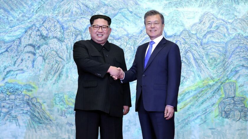 North Korean leader Kim Jong Un, left, shakes hands with South Korean President Moon Jae-in at the Peace House in the border village of Panmunjom on Friday.
