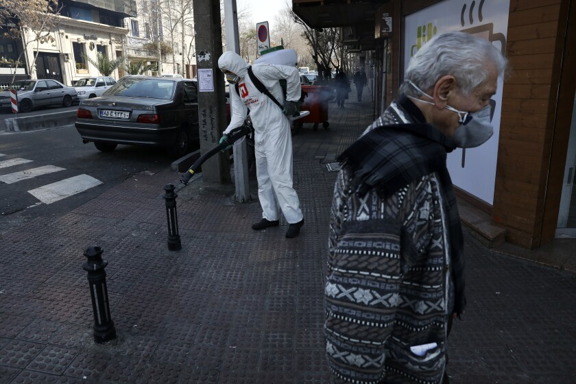 A firefighter disinfects a sidewalk against the new coronavirus as a man wearing face mask walk in Tehran, Iran, Thursday, March 5, 2020. Iran has one of the highest death tolls in the world from the new coronavirus outside of China, the epicenter of the outbreak. (AP Photo/Vahid Salemi)