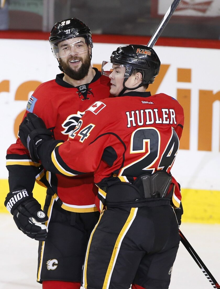 Calgary Flames' Deryk Engelland, left, celebrates his goal against the Minnesota Wild with teammate Jiri Hudler, from the Czech Republic, during the second period of an NHL hockey game Wednesday, Feb. 17, 2016, in Calgary, Alberta. (Larry MacDougal/The Canadian Press via AP)