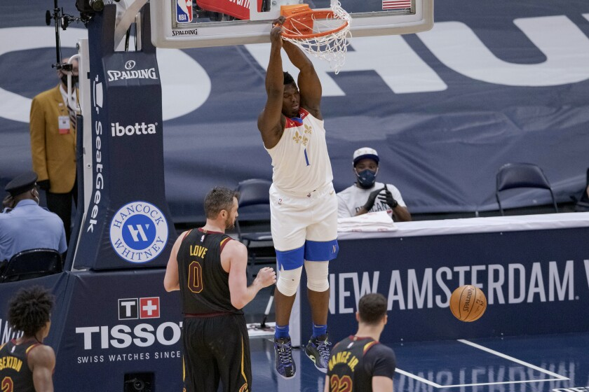 New Orleans Pelicans forward Zion Williamson (1) dunks against Cleveland Cavaliers forward Kevin Love (0) during the first half of an NBA basketball game in New Orleans, Friday, March 12, 2021. (AP Photo/Matthew Hinton)