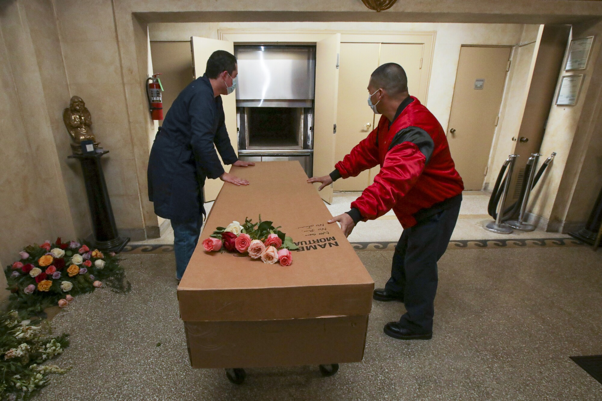 A pair of workers handle a cardboard container topped with roses