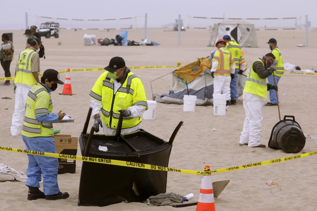 Los Angeles city sanitation workers clear homeless encampments on the beach in Venice.