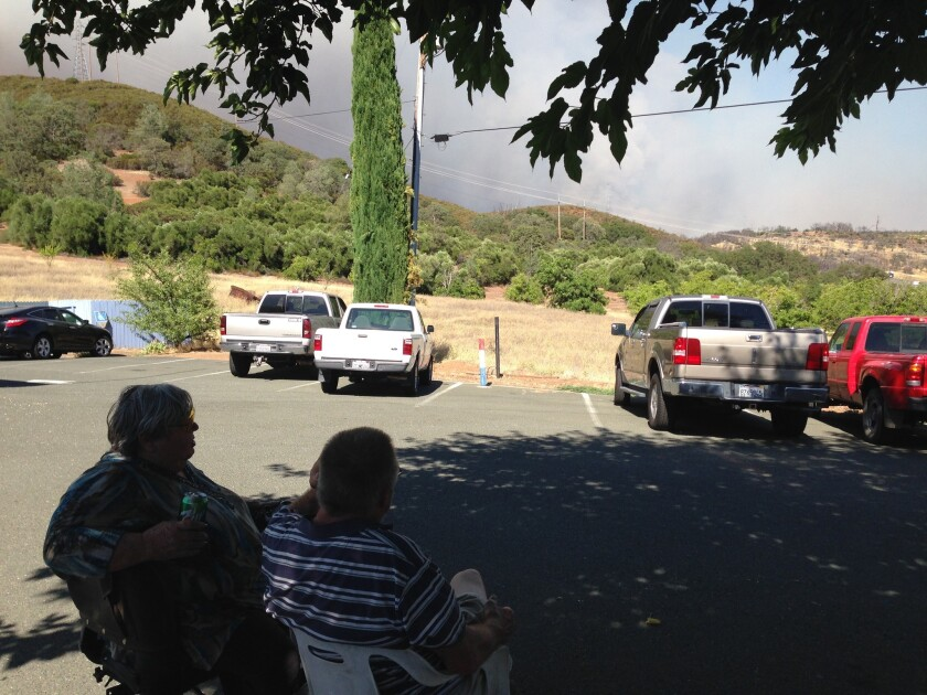 Cheryl and Chris Christian, who live in Clearlake Oaks, Calif., watch the smoke billowing from their neighborhood on Monday afternoon. The Rocky fire has forced thousands of evacuations.