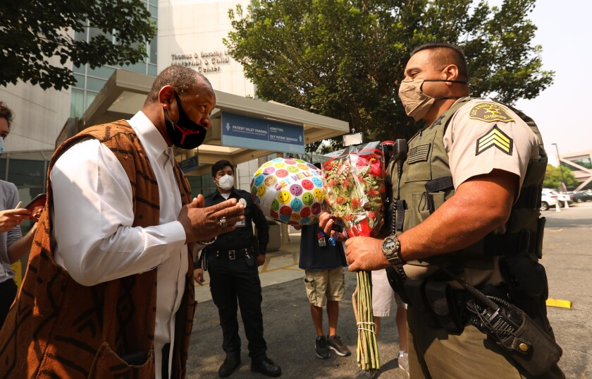 """Community activist Najee Ali gives L.A. County sheriff's Larry Villareal flowers and a """"get well"""" balloon."""