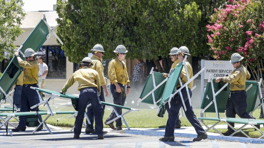 RIDGECREST, CA - JULY 04, 2019 ? Fire fighters placing cots for patients that are being evacuated from Ridgecrest Regional Hospital after city was hit by a 6.4 earthquake Thursday July 04, 2019 morning. (Irfan Khan / Los Angeles Times)