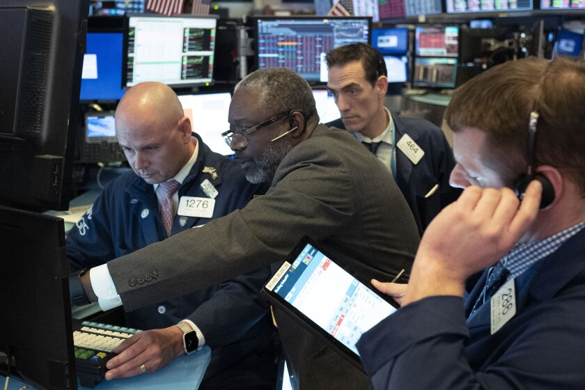 Traders at the New York Stock Exchange work as the market closes Wednesday.