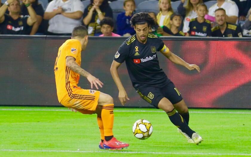 LAFC captain Carlos Vela dekes Houston Dynamo midfielder Matias Vera.