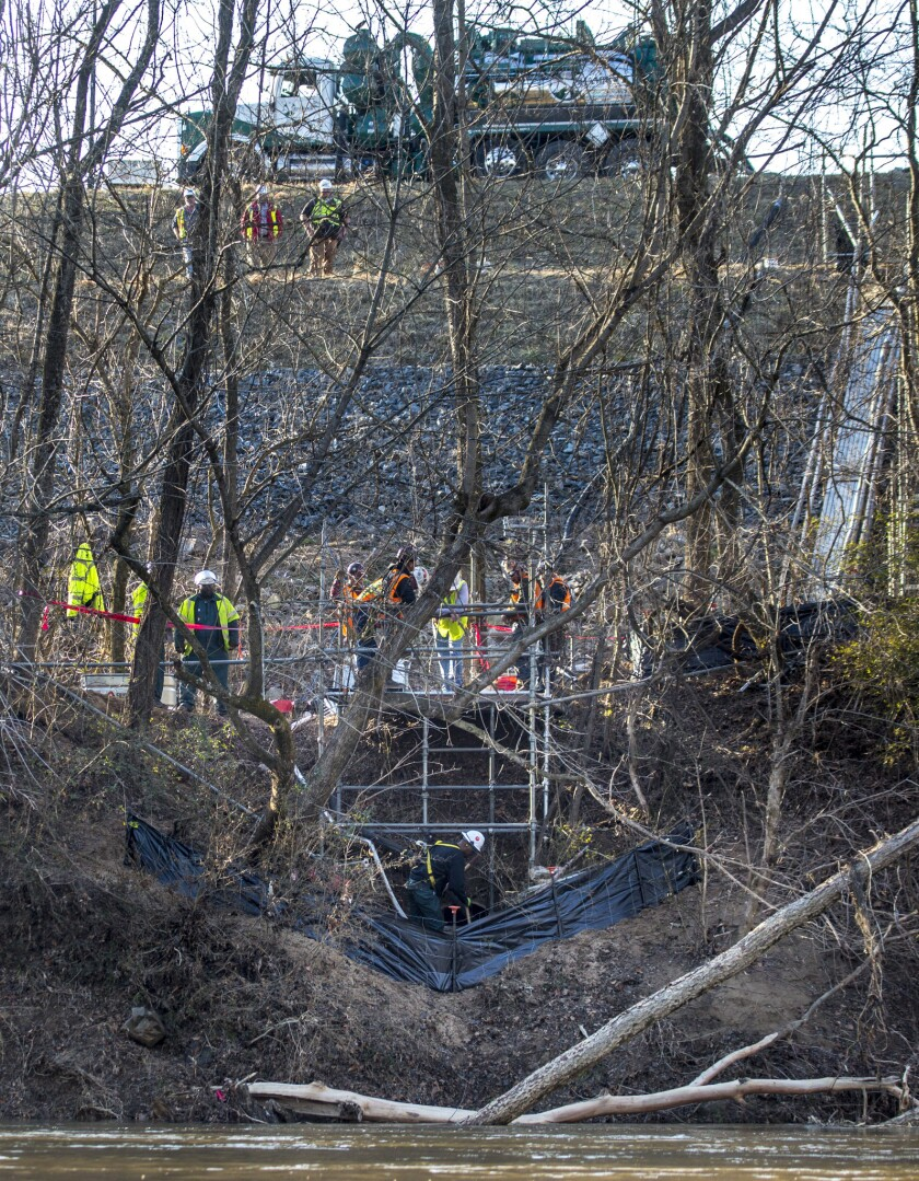 Workers with Duke Energy on Wednesday work to seal a pipe leaking coal ash into the Dan River in North Carolina. On Friday state officials announced the leak had been plugged.