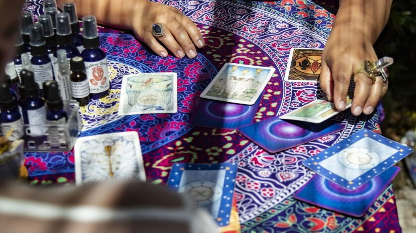 LOS ANGELES, CA - JUNE 29, 2019: Reina Prado, top, reads Tarot cards for a customer during a summer
