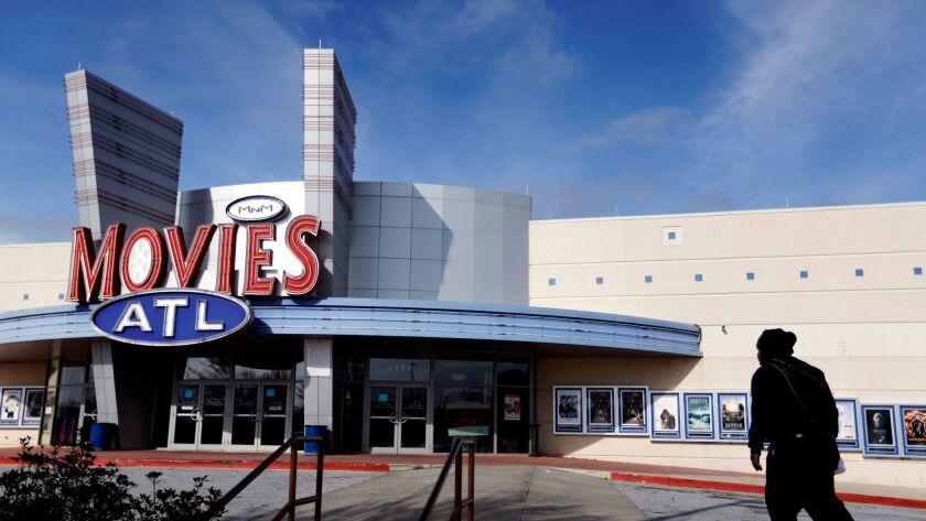 A patron walks into a Carmike Cinemas movie theater in Atlanta