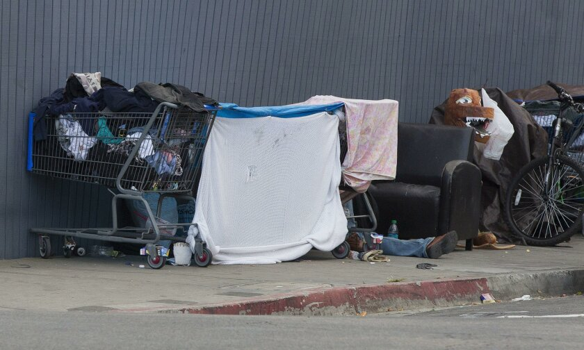 In this 2015 file photo, homeless people along Commercial Street in downtown San Diego set up shelters before the sun sets. City rules limit daytime camping in some areas.