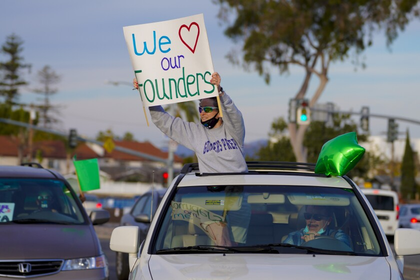 """Gompers Preparatory Academy supporters raise signs like this one saying """"We love our founders"""" Tuesday."""