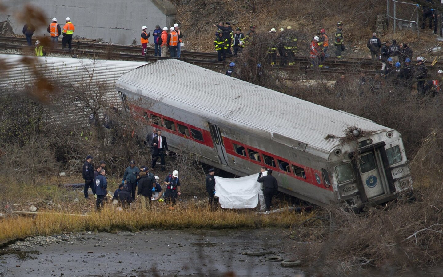 Viewed from Manhattan, first responders and others work at the scene of a  derailed Metro North passenger train in the Bronx borough of New York Dec. 1, 2013. The train derailed on a curved section of track in the Bronx early Sunday, coming to rest just inches from the water, killing at least four