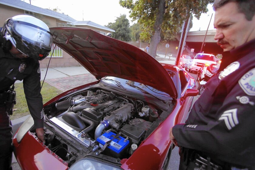 Officer Will Durr, left, and Sgt. Greg Fuqua, members of the Los Angeles Police Department's Aggressive Driving Detail, inspect the illegal modifications a motorist had made to his vehicle in Granada Hills.