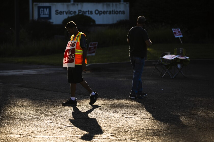 Workers Joel Inocencio, left, and Mike Jones demonstrative outside a General Motors facility in Langhorne, Pa., Tuesday, Sept. 17, 2019. More than 49,000 members of the United Auto Workers walked off General Motors factory floors or set up picket lines early Monday as contract talks with the company deteriorated into a strike. (AP Photo/Matt Rourke)