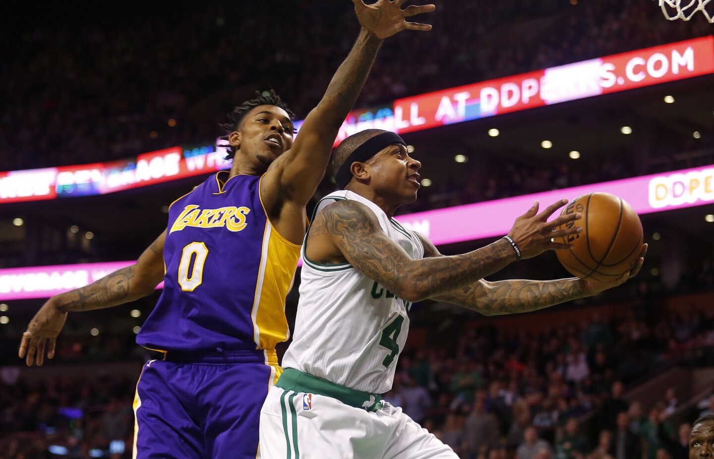 Celtics guard Isaiah Thomas drives past Lakers guard Nick Young for a layup during the first half.