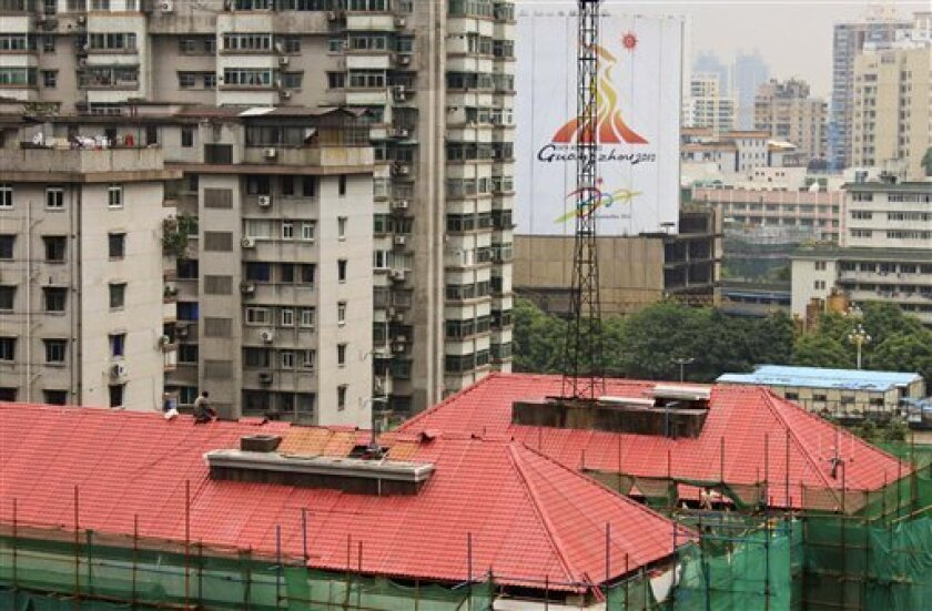 In this photo taken Tuesday, May 18, 2010, workers repaint building roofs near a Guangzhou Asian Games advertisement board in Guangzhou, China. For the past year, workers have been repainting hundreds of buildings in Guangzhou and topping them with pitched roofs made of PVC sheets molded to look li