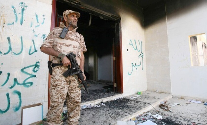 A Libyan military guard stands in front of one of the U.S. Consulate's burned out buildings in Benghazi, Libya, a few days after the attack on the compound.